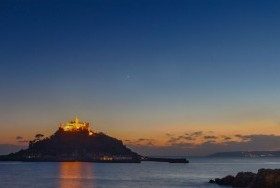 View from the restaurant of sunset over a lit up St Michael's Mount